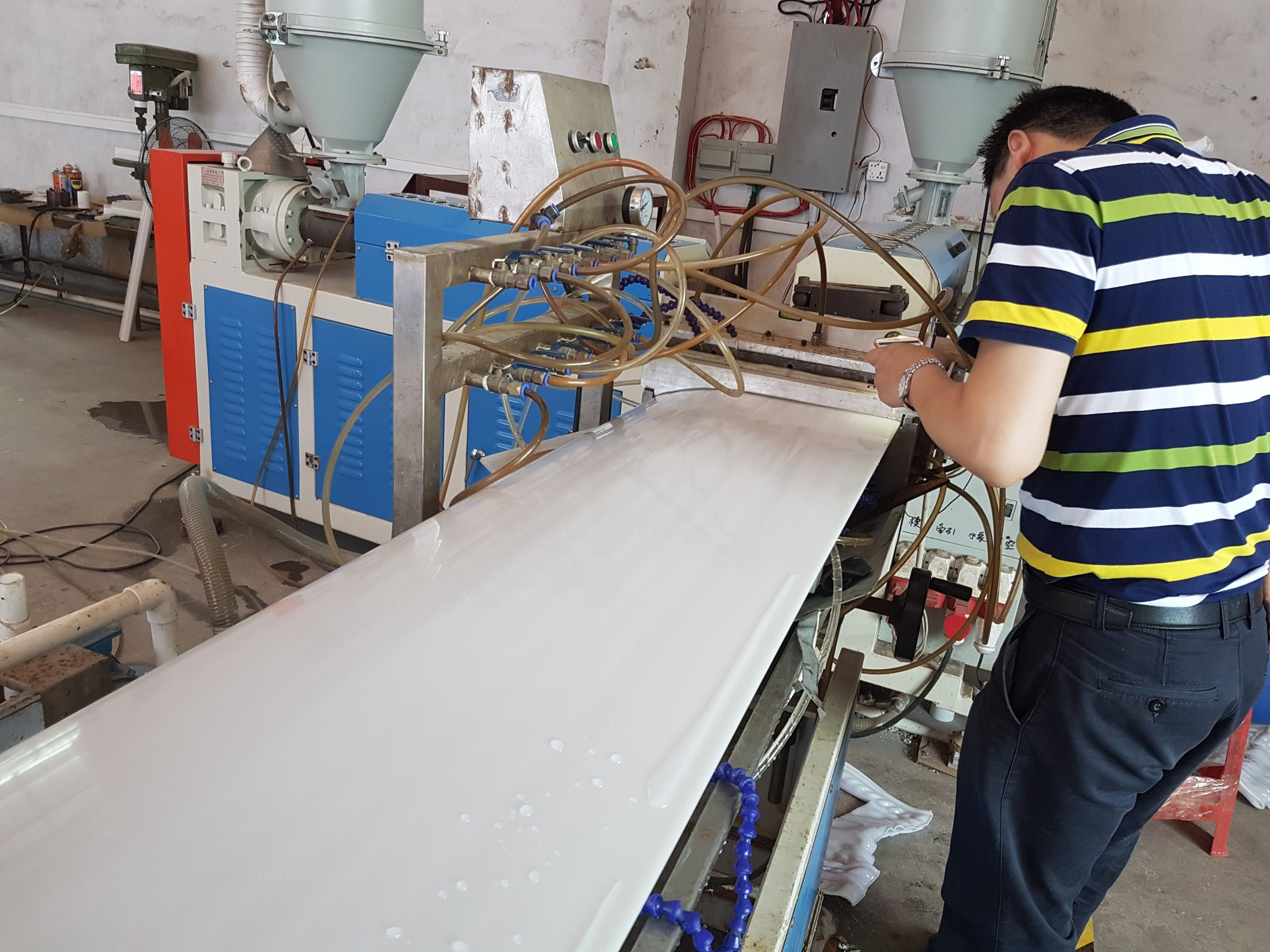 A factory worker using machinery to manufacture a custom cabinet door.